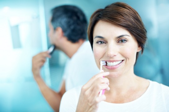 Smiling mature woman brushing her teeth while her partner shaves - portrait